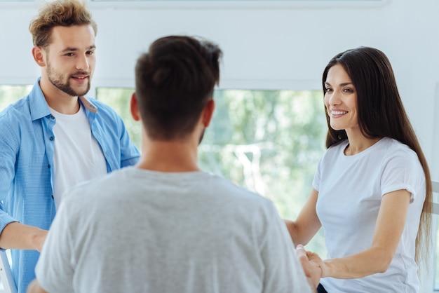 Pessoas alegres e positivas sorrindo e olhando umas para as outras durante uma sessão psicológica