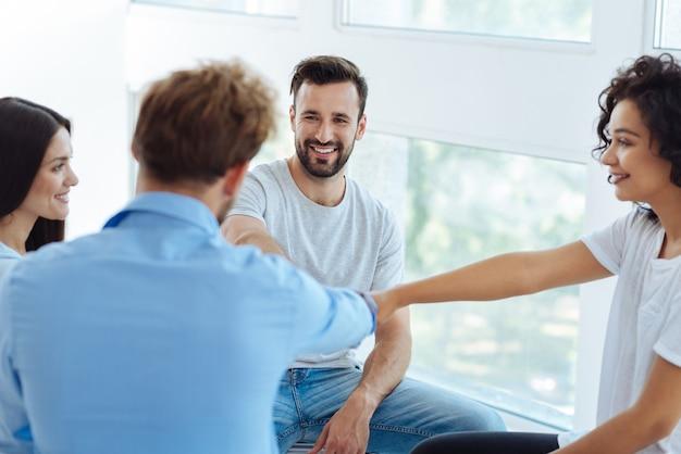 Pessoas alegres e simpáticas sorrindo e fazendo uma atividade de teambuilding enquanto visitam um seminário de teambuilding