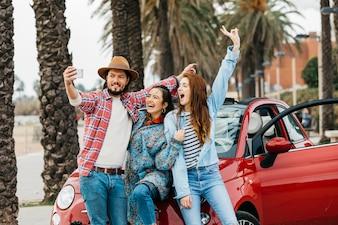 Pessoas alegres tomando selfie perto de carro vermelho na rua