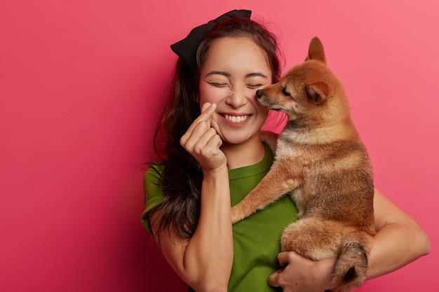 Pessoas, amam o conceito de animais. menina coreana positiva brinca com cachorro shiba inu, fazendo mini gesto de coração