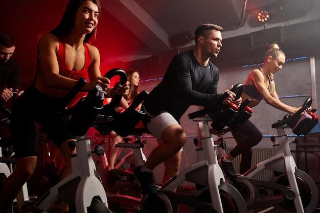 Pessoas andando de bicicleta na aula de spinning no ginásio moderno, fazendo exercícios em bicicleta ergométrica. grupo de atletas caucasianos treinando em bicicleta ergométrica