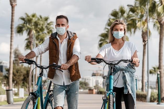 Pessoas andando de bicicleta usando uma máscara médica