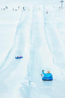 Pessoas andando em tubos de neve no espaço da cópia do parque de inverno