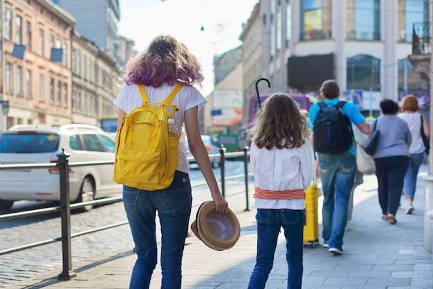 Pessoas andando em uma rua da cidade, calçada, estrada com carros em movimento.
