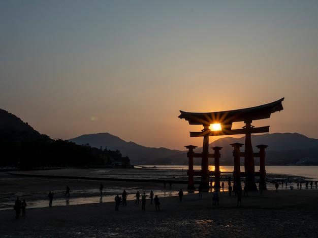 Pessoas andando perto do grande torii santuário de itsukushima de miyajima ao pôr do sol