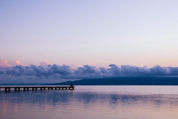 Pessoas anônimas sentadas no cais perto do mar ao pôr do sol