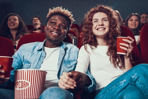 Pessoas apaixonadas assistindo filme no cinema.