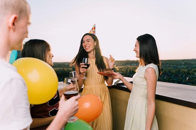 Pessoas apreciando vinho e bolo no telhado
