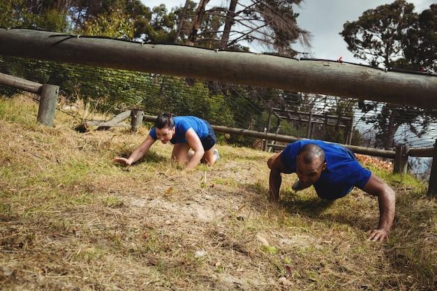 Pessoas aptas rastejando sob a rede durante a pista de obstáculos