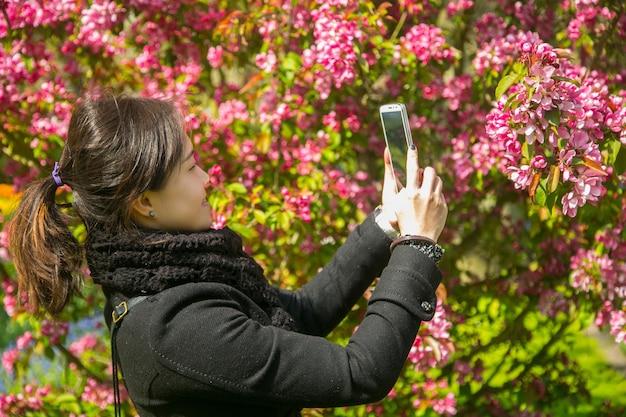Pessoas asiáticas usando smartphone para tirar foto de flor de cerejeira em tóquio, japão.