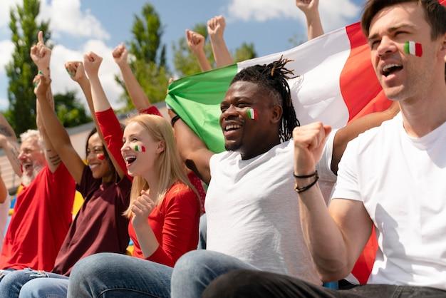 Pessoas assistindo a um jogo de futebol juntas
