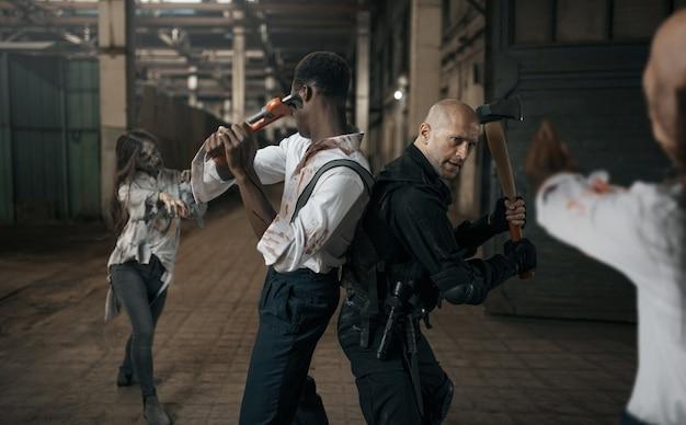 Pessoas assustadas lutam com o exército de zumbis em uma fábrica abandonada. terror na cidade, rastejadores assustadores, apocalipse do fim do mundo, monstros malignos sangrentos