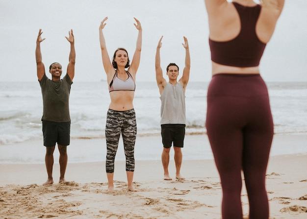 Pessoas atléticas se alongando na praia