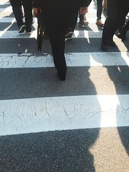 Pessoas atravessando a rua pela faixa de pedestres