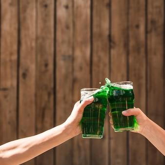 Pessoas batendo copos de bebida verde perto da parede de madeira
