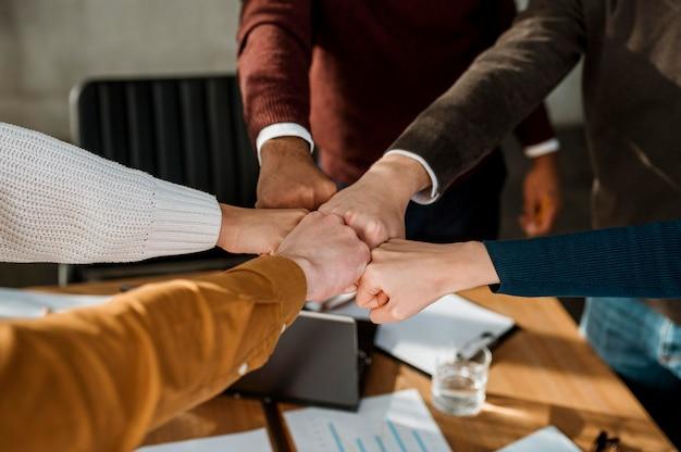 Pessoas batendo os punhos umas nas outras durante uma reunião