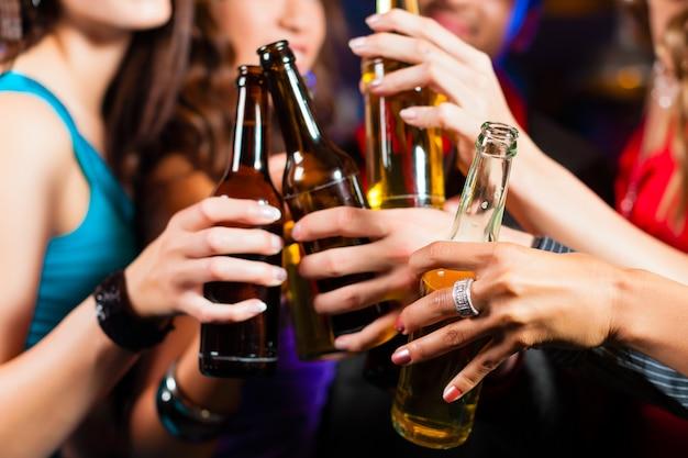 Pessoas bebendo cerveja no bar ou clube