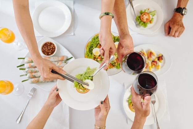Pessoas bebendo vinho e comendo saborosa salada de vegetais e rolinhos primavera no jantar, vista de cima