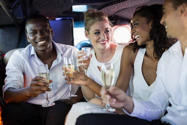 Pessoas bem vestidas, bebendo champanhe em uma limusine