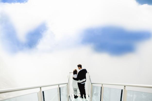 Pessoas bonitas abraçam no céu e nas nuvens