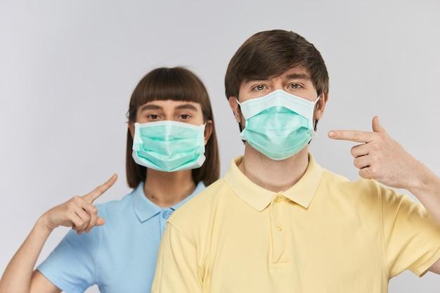 Pessoas bonitas com máscara protetora apontando para ela vestindo camisas amarelas e azuis isoladas em azul, proteja-se contra poluição e coronavírus, copie o espaço