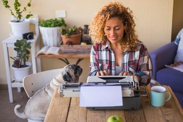 Pessoas bonitas e felizes, mulher loira encaracolada caucasiana trabalhando em uma velha máquina de escrever ao ar livre em uma mesa rústica e de madeira com o cão pug melhor amigo olhando para ela com amor