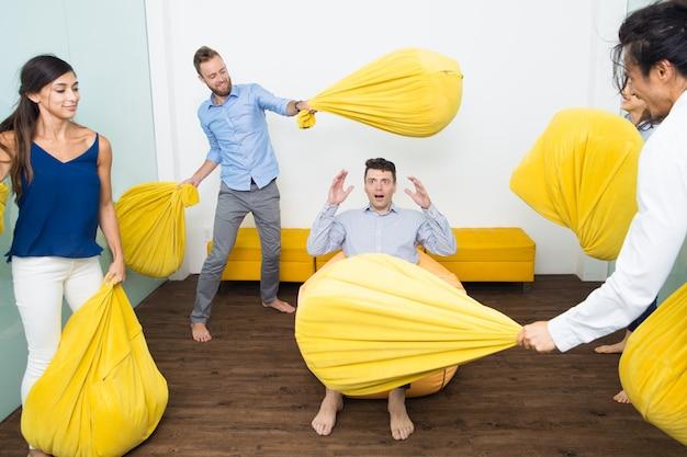 Pessoas brincadeiras batendo seu amigo com travesseiros
