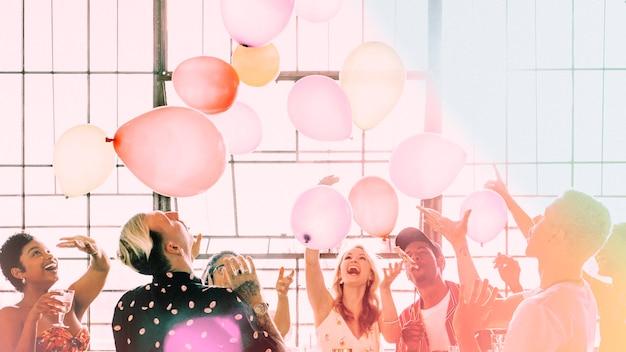 Pessoas brincando com balões em um papel de parede de festa