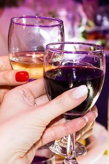 Pessoas brindam com vinho tinto e branco. taças de vinho nas mãos de mulheres, alcoolismo feminino, feriado feminino