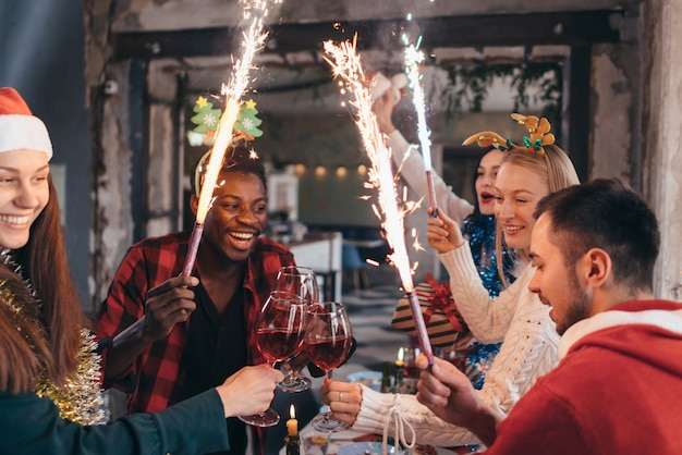 Pessoas brindando champanhe, comemorando com fogos de artifício e se olhando sorrindo.