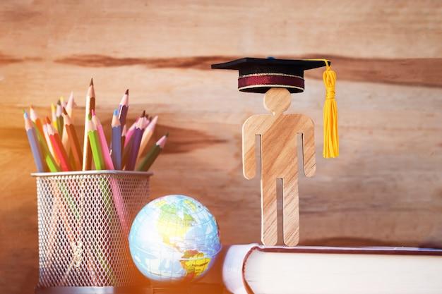 Pessoas cadastre-se de madeira com graduação celebrando boné no livro didático