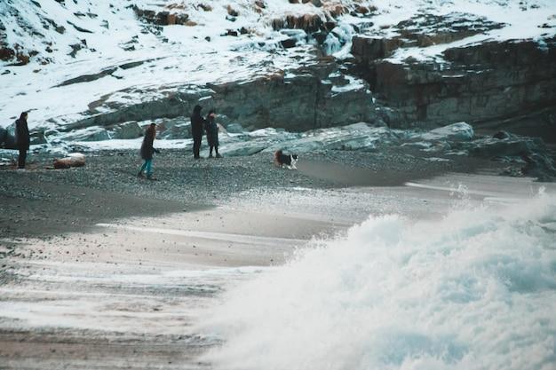 Pessoas caminhando em um campo coberto de neve durante o dia