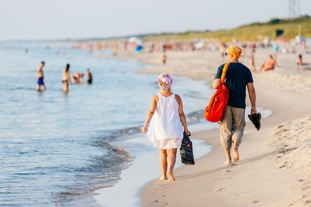 Pessoas caminhando na praia perto do mar no verão.