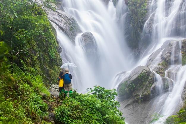 Pessoas caminhando perto da cachoeira