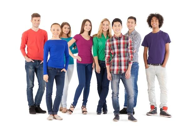 Pessoas casuais. comprimento total de jovens alegres, sorrindo para a câmera em pé, isolado no branco