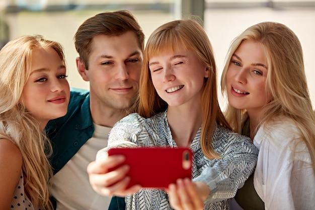Pessoas caucasianos felizes posando para uma foto em um café juntos