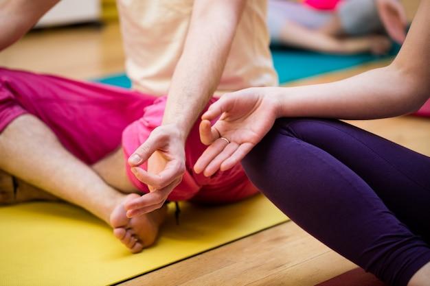 Pessoas com as pernas cruzadas em um ginásio e fazendo um círculo com as mãos