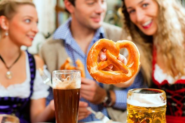 Pessoas com cerveja e pretzel no pub da baviera