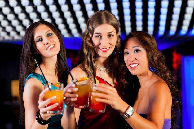 Pessoas com cocktails no bar ou clube
