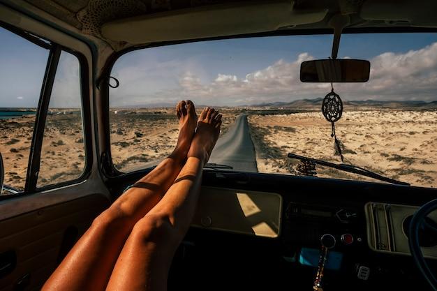 Pessoas com conceito de viagens e liberdade com pernas de mulher de perto aproveitam a viagem dentro de uma van vintage velha - garota de estilo de vida vanlife com asfalto de estrada longa no fundo