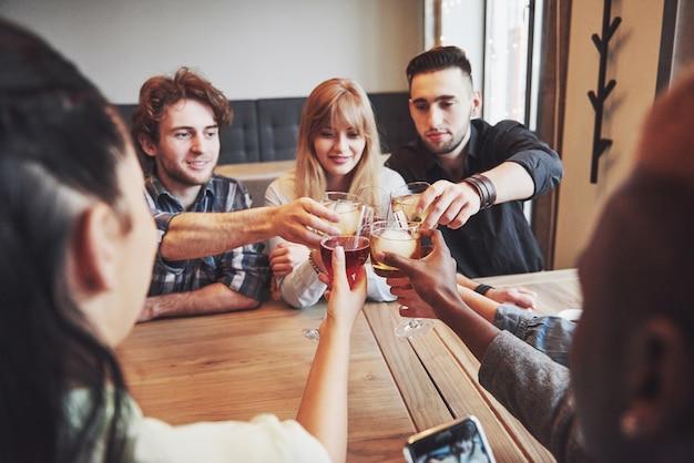 Pessoas com copos de uísque ou vinho comemorando e brindando