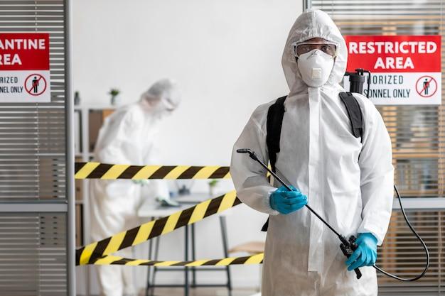 Pessoas com equipamento de proteção desinfetando uma área perigosa