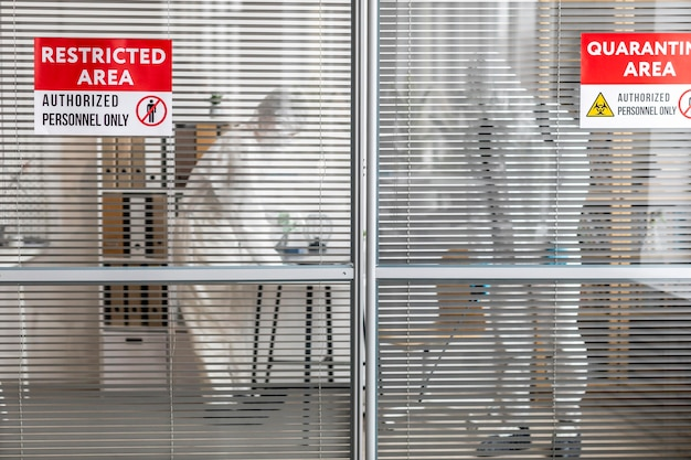 Pessoas com equipamento de proteção desinfetando uma área perigosa Foto gratuita