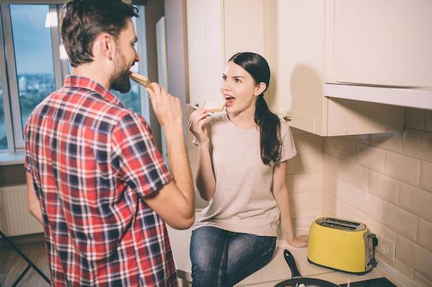 Pessoas com fome estão na cozinha. garota senta-se e brinda brinde. guy olha para ela e faz a mesma coisa. eles comem pedaços de pão.