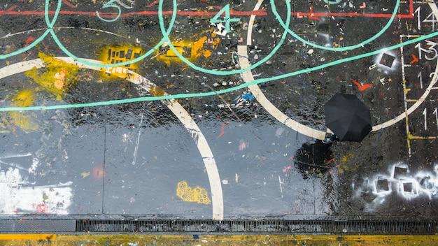 Pessoas com guarda-chuva caminha na rua escura pedestre na vista aérea superior na temporada de chuva e água no chão.