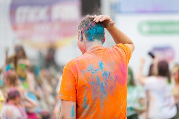 Pessoas com impressões de mãos feitas com cores holi em suas roupas coloridas durante o holi festival, festival of colors