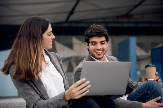Pessoas com laptop ao ar livre plano médio