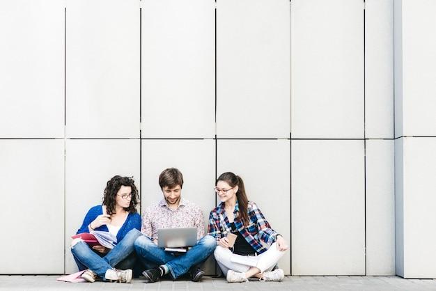 Pessoas com livros e gadgets sentados no chão perto da parede. conceito de mídia social de educação.
