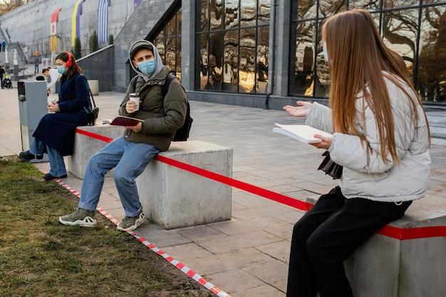 Pessoas com máscara distantes umas das outras