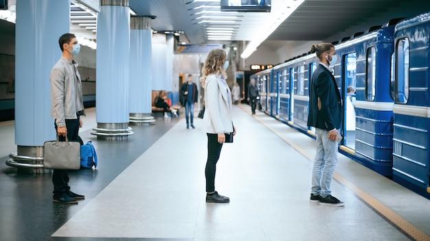 Pessoas com máscaras de proteção em pé na plataforma do metrô